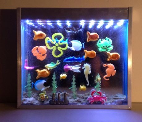 John Bohac. Aquarium. Toys, sand, plastic resin, plexiglas, aluminum, LEDs. 13x15 in. 2014