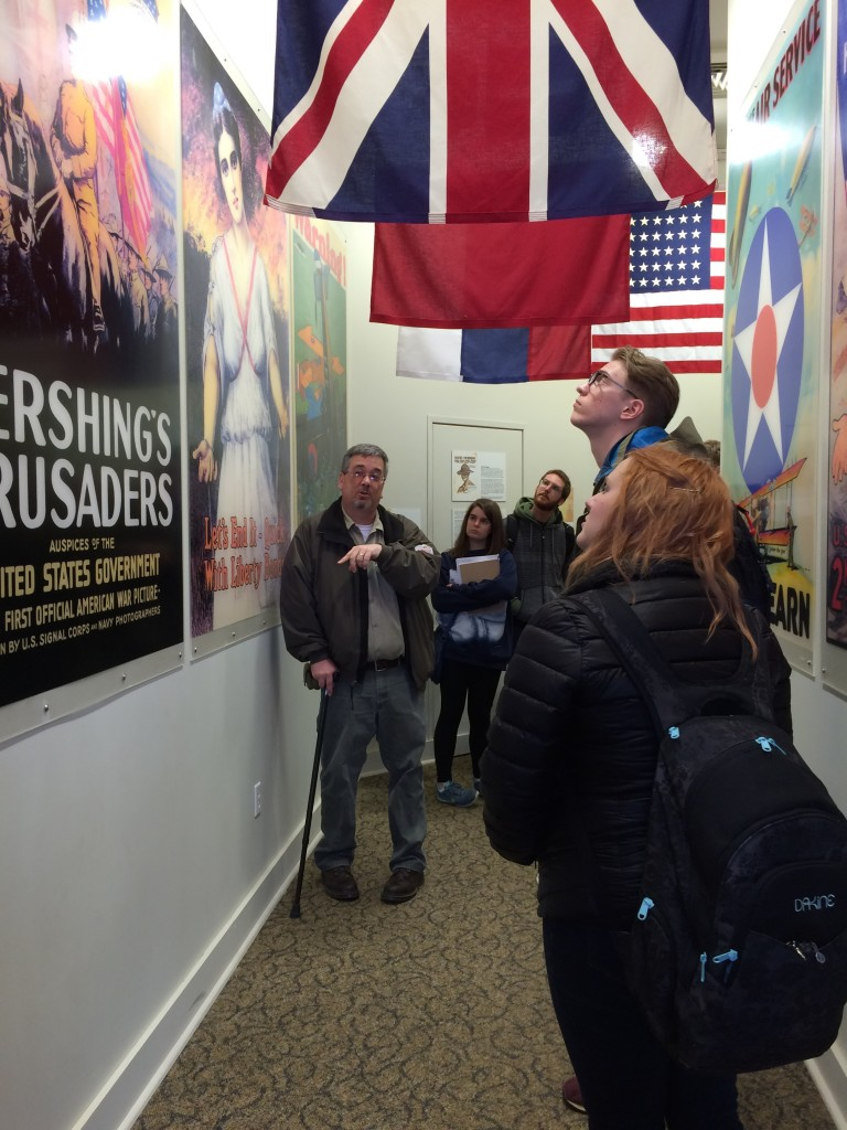 Denzil Heaney, Administrator and Curator of the General John J. Pershing Boyhood Home State Historic Site in Lacelede, Missouri, discusses the array of World War I poster images on display in one of the exhibition spaces at the site. Truman students shown are, from left to right, Rachel Pozzo, Anthony LaMarche, Luke Edwards, and Victoria Loos.