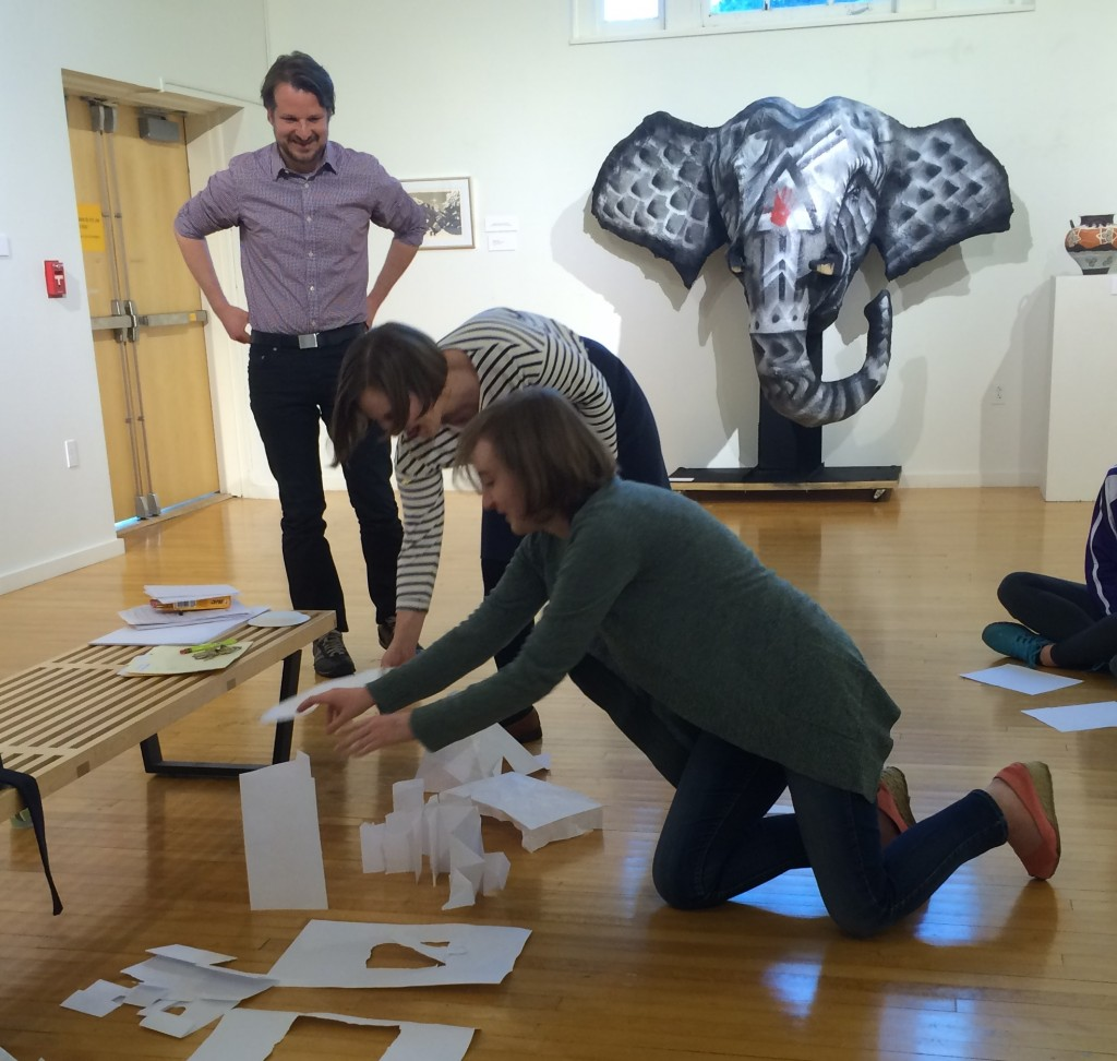 Mike Murawski, Heidi Cook (Gallery Director), and Emma Shouse setting up torn and folded paper responses to a quilt in the University Gallery.