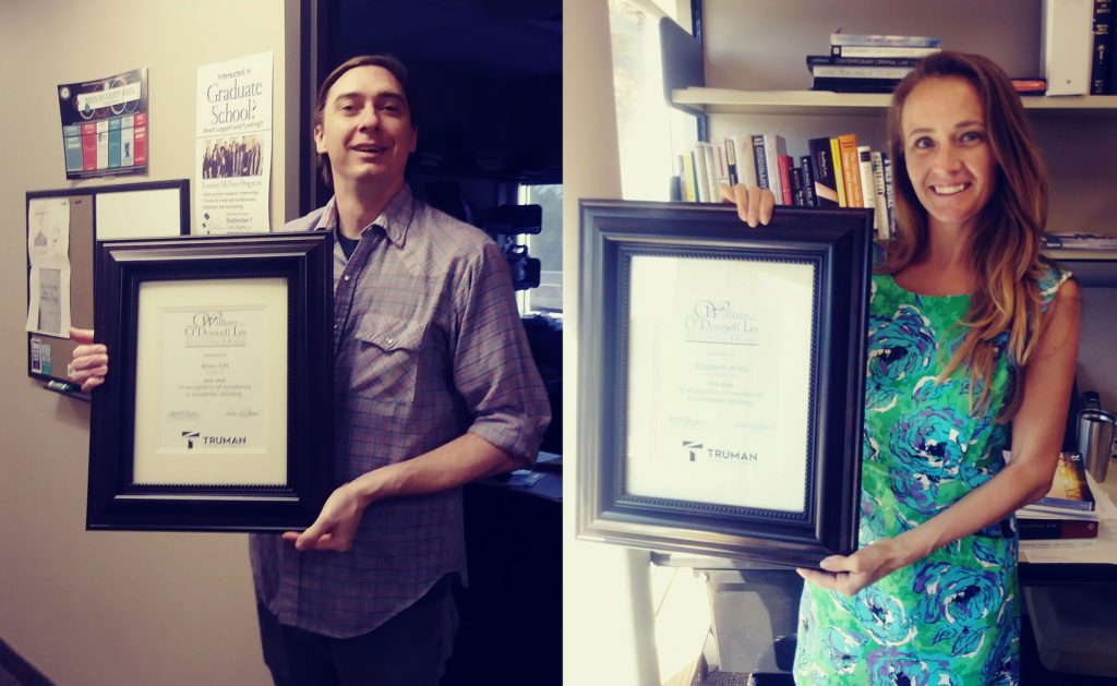 Two professors holding up their framed awards